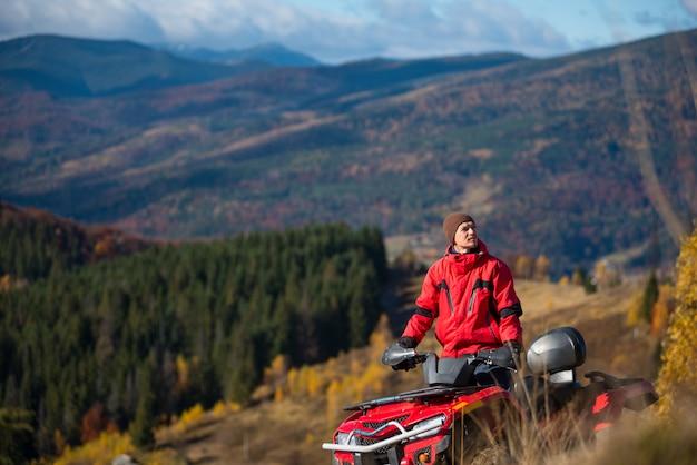 Cara andando em quad bike nas montanhas Foto Premium