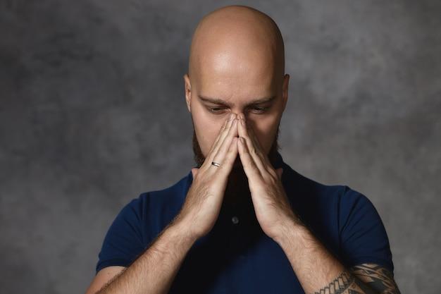 Cara barbudo com a cabeça raspada com resfriado, segurando as mãos perto do nariz como se fosse espirrar. homem careca sentindo-se deprimido cobrindo o rosto, ponderando, em busca de solução para o problema. linguagem corporal Foto gratuita