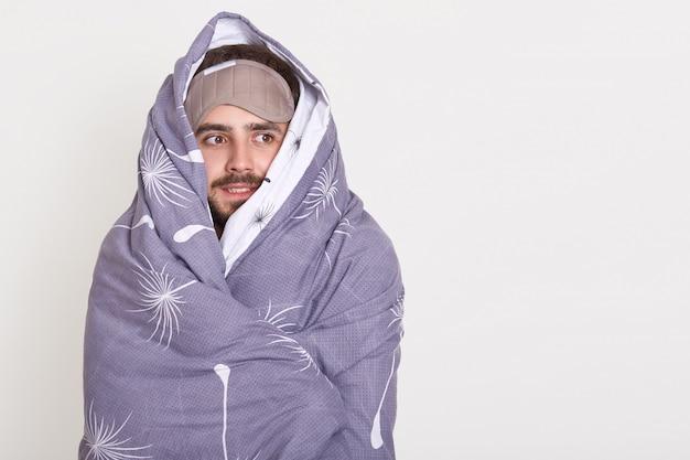 Cara barbudo com máscara de dormir na testa, olhando de lado, sendo embrulhado no cobertor, cópia espaço anúncio ou promoção de texto Foto gratuita