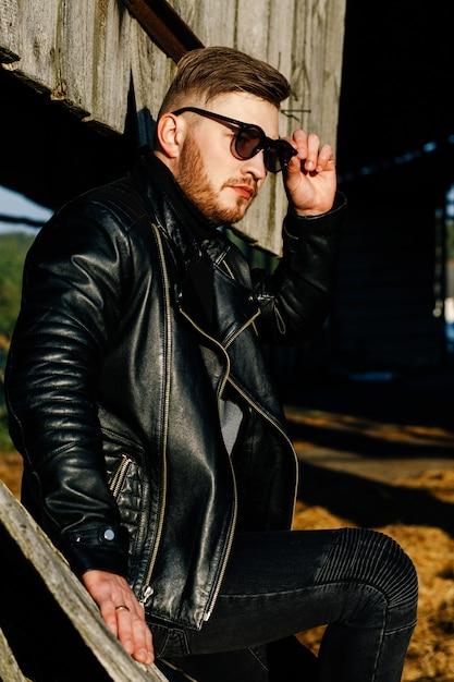 Cara barbudo de óculos escuros em uma jaqueta de couro senta-se no fundo de uma parede de madeira velha Foto Premium