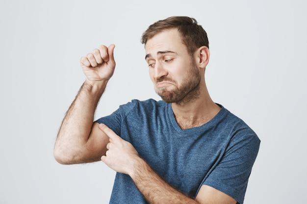 Cara barbudo insatisfeito flexiona os bíceps fracos, sem força Foto gratuita