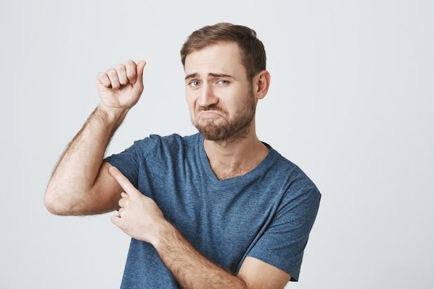 Cara barbudo insatisfeito flexionar os bíceps fracos, precisa ir à academia Foto gratuita