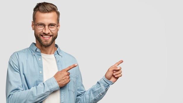 Cara barbudo positivo posando contra a parede branca Foto gratuita