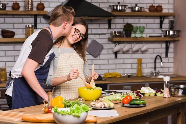 Cara, beijando, mulher jovem, misturando salada, em, cozinha Foto gratuita