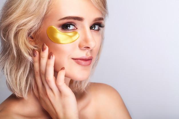 Cara bonita da mulher com os remendos do hidrogel do ouro, levantando a máscara do colagénio do anti-ruga na pele facial saudável fresca. Foto Premium