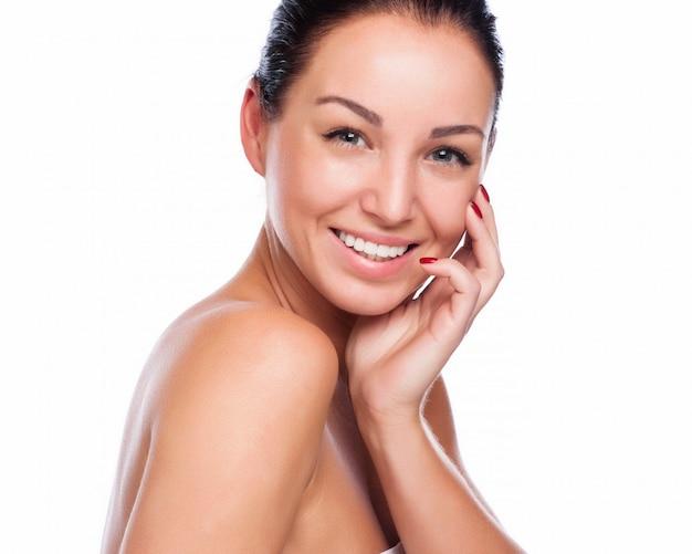 Cara bonita da mulher de sorriso bonita - levantando no estúdio isolado no branco Foto Premium