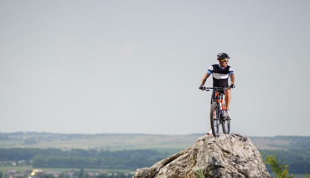 Cara bonito com bicicleta no topo da montanha Foto Premium