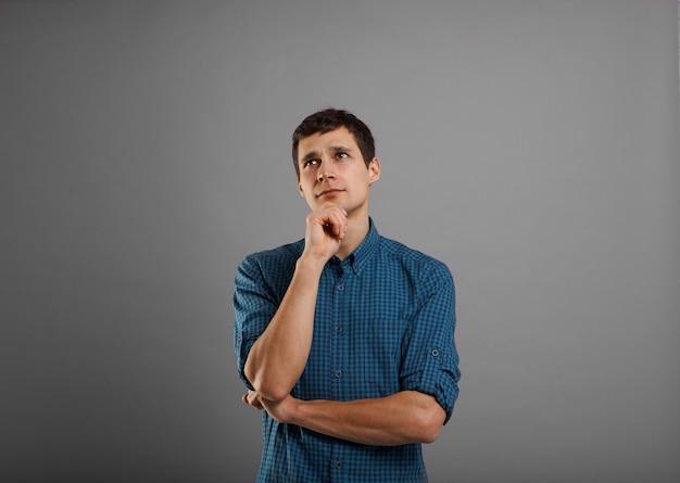 Cara bonito de camisa azul pensando Foto gratuita