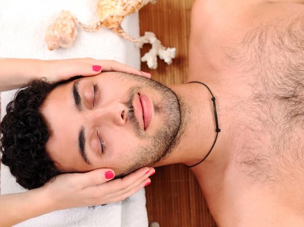 Cara bonito, desfrutando de terapia de massagem Foto gratuita