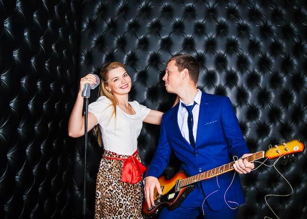 Cara bonito e menina cantando no microfone no estúdio Foto Premium