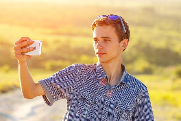 Cara bonito leva um selfie no telefone ao sol Foto Premium