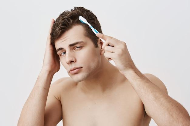Cara bonito musculoso com penteado da moda, pele saudável, fazendo caretas, se divertindo dentro de casa, usando a escova de dentes para pentear o cabelo escuro. modelo masculino nu atraente olhando com apelo Foto gratuita