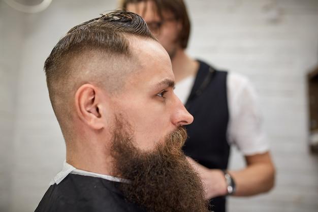 Cara brutal na barbearia moderna. cabeleireiro faz penteado um homem com uma barba longa. mestre cabeleireiro faz penteado com máquina de cortar cabelo Foto Premium