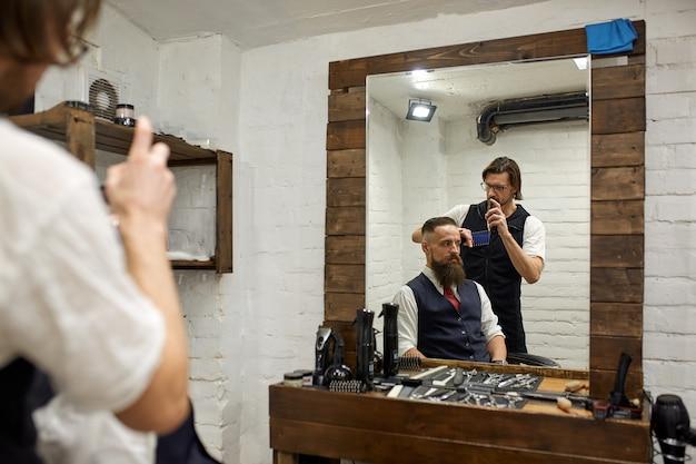 Cara brutal na barbearia moderna. cabeleireiro faz penteado um homem com uma barba longa. mestre cabeleireiro faz penteado por tesoura e pente Foto Premium