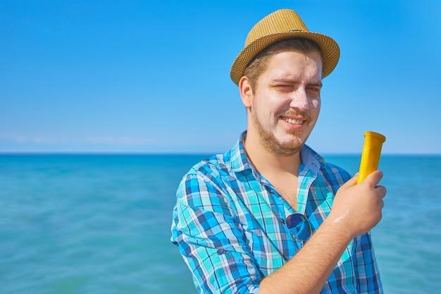 Cara colocando loção de proteção onsun no rosto. um homem à beira-mar, com o rosto manchado de protetor solar. Foto Premium