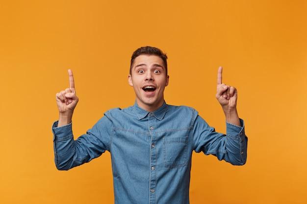 Cara com a boca aberta de surpresa mostra com os dedos indicadores Foto gratuita