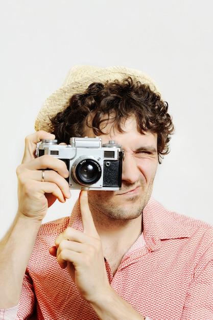 Cara com cabelo encaracolado com uma câmera em um fundo branco Foto Premium