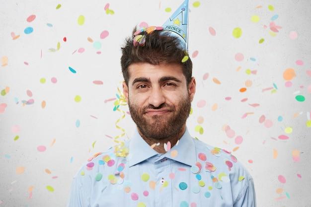 Cara com chapéu de festa e confete Foto gratuita