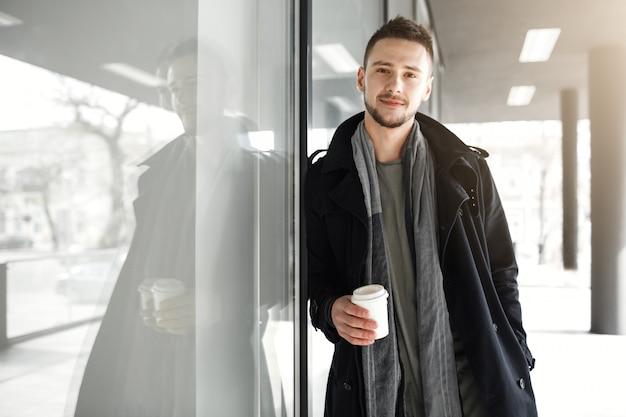 Cara com roupas de primavera legal relaxante enquanto bebe café lá fora. Foto gratuita
