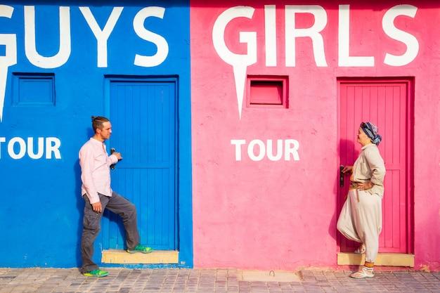 Cara com uma garota perto de uma parede engraçada incomum. o conceito de diferenças de gênero. Foto Premium