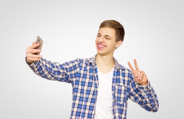 Cara de camisa azul faz uma selfie no telefone Foto Premium