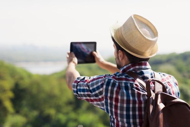 Cara de chapéu e com mochila para viajar faz a phography. Foto Premium