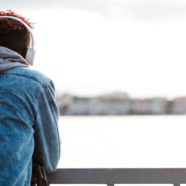 Cara de close-up com fones de ouvido perto de um lago Foto gratuita