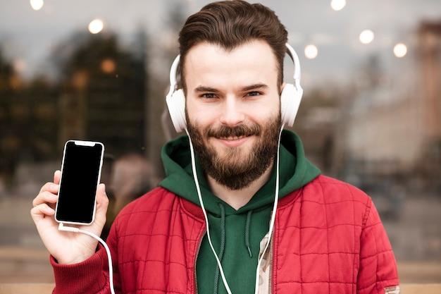 Cara de close-up com fones de ouvido segurando smartphone Foto gratuita