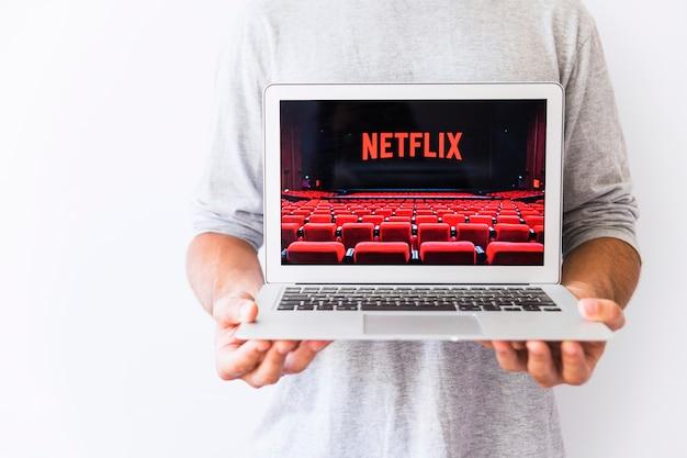 Cara de colheita segurando laptop com o logotipo da netflix Foto gratuita