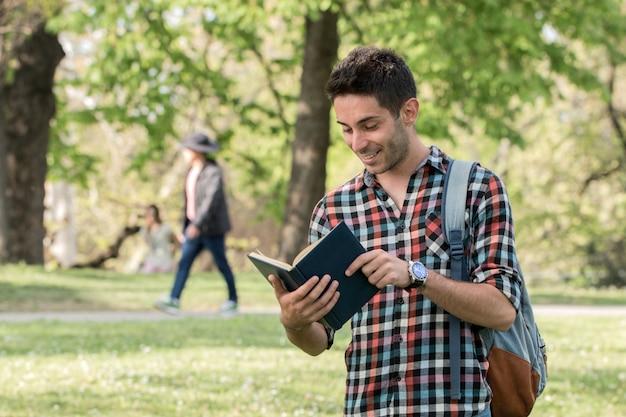 Cara de estudante fazendo lição de casa no parque. Foto Premium