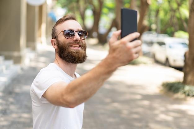 Cara de hipster alegre tomando selfie Foto gratuita