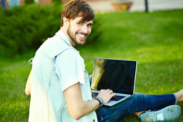 Cara de homem bonito hipster sorridente engraçado em pano elegante de verão na grama com notebook Foto gratuita