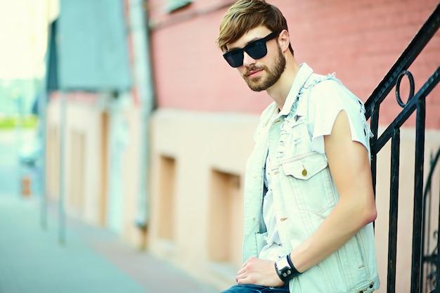 Cara de homem bonito hipster sorridente engraçado em pano elegante de verão na rua em óculos de sol Foto gratuita