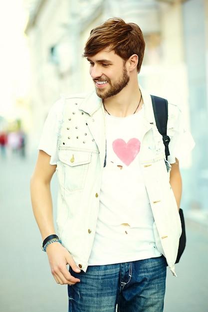 Cara de homem bonito hipster sorridente engraçado em pano elegante de verão na rua Foto gratuita