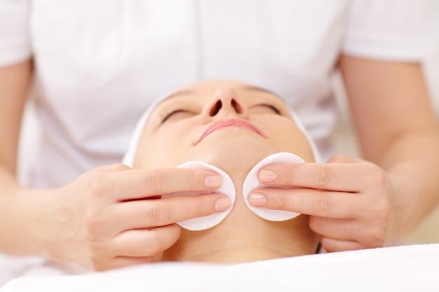 Cara de limpeza cosmético usando almofadas de algodão Foto Premium