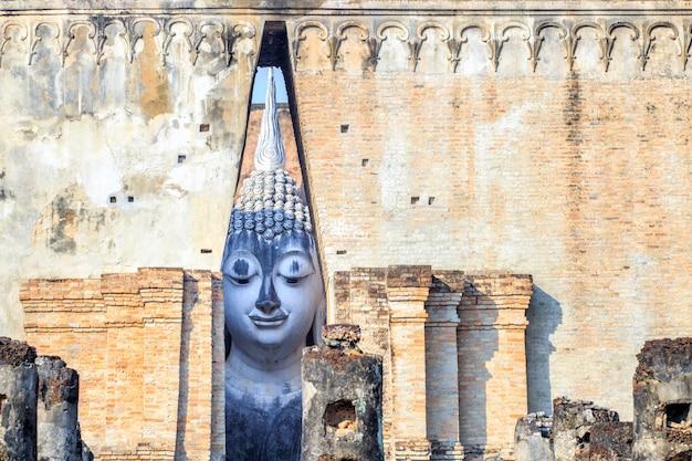 Cara de sorriso grande da estátua de buddha no parque histórico de sukhothai, templo de sri chum, tailândia Foto Premium