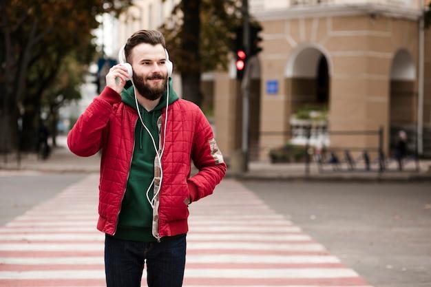 Cara de tiro médio com fones de ouvido atravessando a rua Foto gratuita