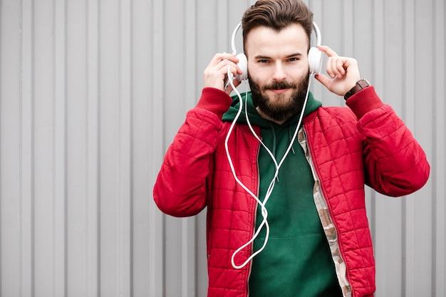 Cara de tiro médio com fones de ouvido e jaqueta vermelha Foto gratuita