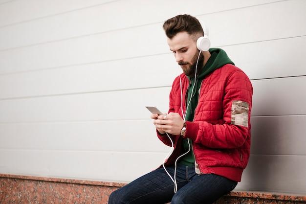 Cara de tiro médio com fones de ouvido e smartphone Foto gratuita