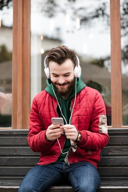Cara de tiro médio com fones de ouvido, sentado em um banco Foto gratuita