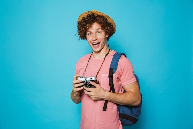 Cara de turista sorridente com cabelos cacheados, usando mochila e chapéu de palha fotografando na câmera retro Foto Premium