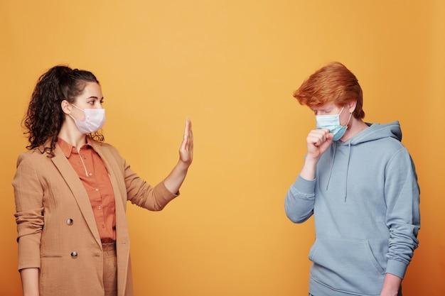 Cara doente com máscara protetora tossindo na frente de uma jovem, mostrando um gesto de parada disposta a evitar doenças infecciosas Foto Premium