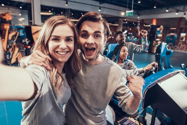 Cara e menina loira no arcade. casal está tomando selfie. Foto Premium