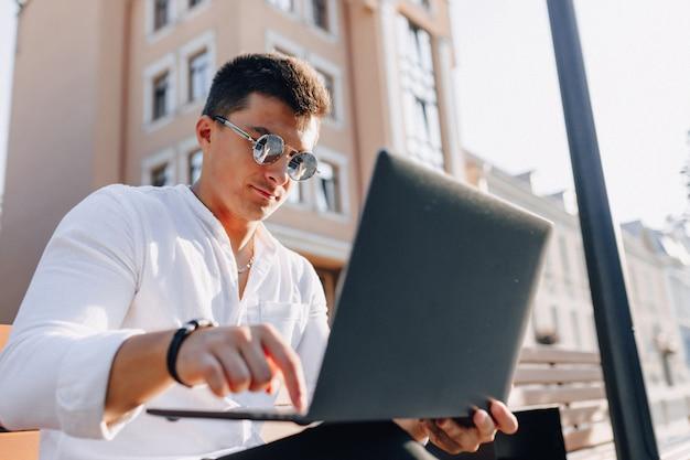 Cara elegante jovem de camisa com telefone e notebook no banco ensolarado dia quente ao ar livre, freelance Foto Premium