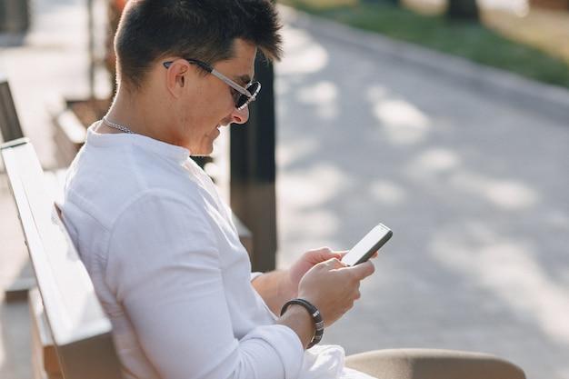 Cara elegante jovem de camisa com telefone no banco ensolarado dia quente ao ar livre Foto Premium
