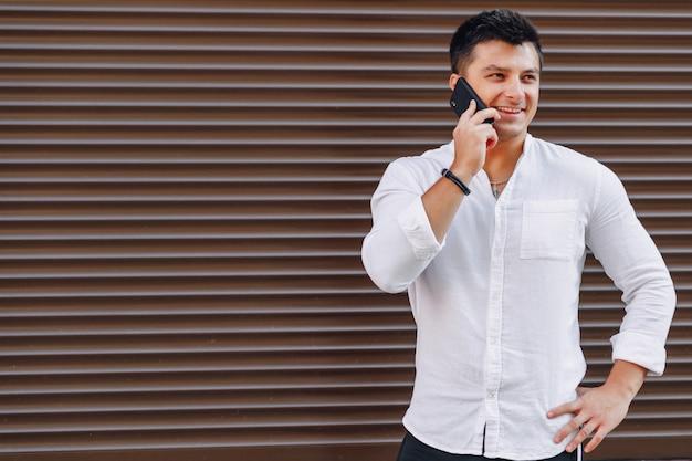 Cara elegante jovem de camisa falando por telefone em fundo simples Foto Premium