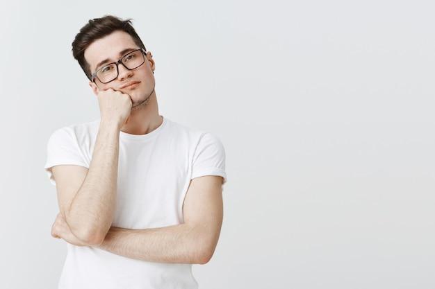 Cara entediado e relutante de óculos, apoiado na mão e olhando sem interesse Foto gratuita