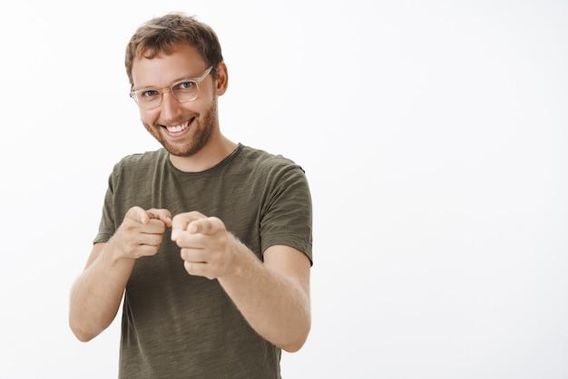 Cara entusiasmado, feliz e confiante com cerdas nos óculos e uma camiseta verde-escura apontando com o dedo como se estivesse escolhendo um candidato com um largo sorriso satisfeito Foto gratuita