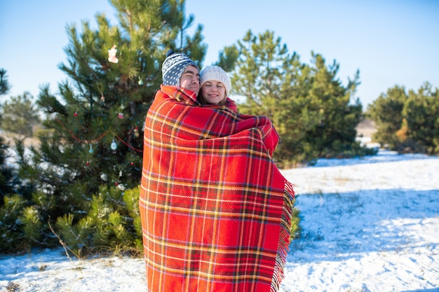 Cara envolve sua namorada em uma manta quadriculada vermelha quente para que ela se aqueça Foto Premium