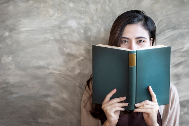 Cara escondendo da mulher bonita atrás do livro verde ao olhar a câmera. Foto Premium